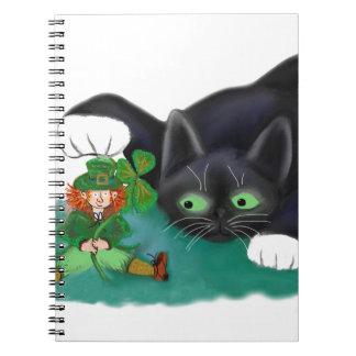 Black and White Tuxedo Kitten Tags his Leprechaun Notebook