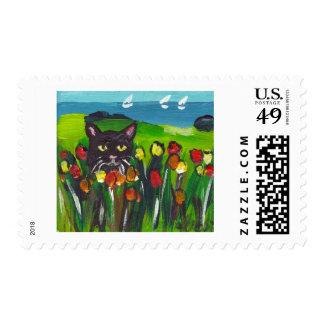Black cat amongst tulips postage