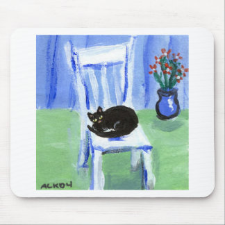 Black cat naps on chair mouse pad
