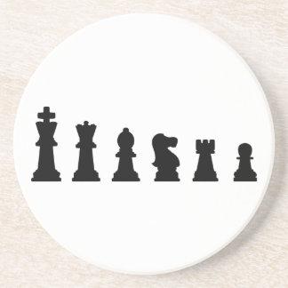Black chess pieces on white coaster