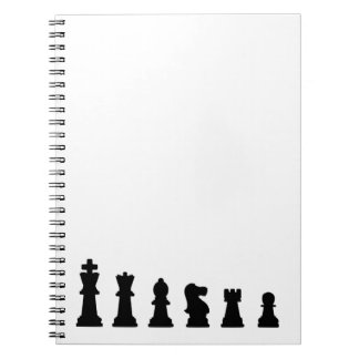 Black chess pieces on white spiral note book