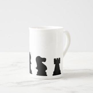 Black chess pieces on white tea cup