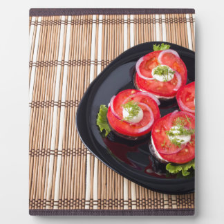 Black dish with sliced tomatoes and lettuce plaque