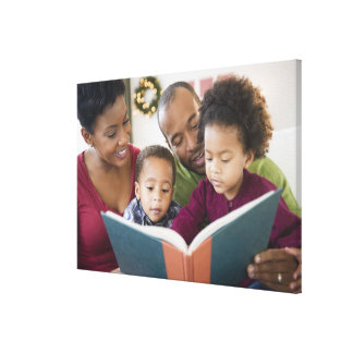 Black family reading book together canvas print