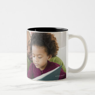 Black family reading book together Two-Tone coffee mug
