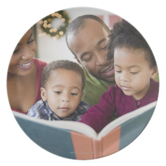 Black family reading book together plate