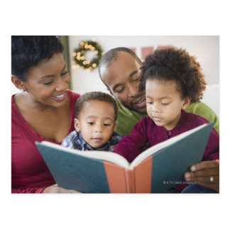 Black family reading book together postcard