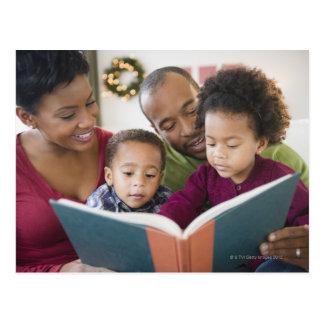 Black family reading book together postcard