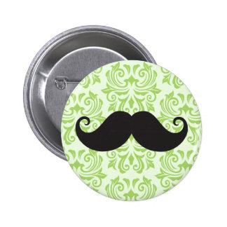 Black handlebar mustache on green damask pattern pinback button