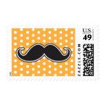 Black handlebar mustache on orange polka dots postage stamps