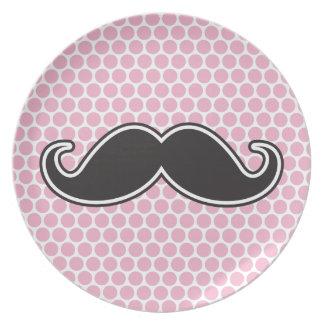 Black handlebar mustache on pink polka dot pattern dinner plate