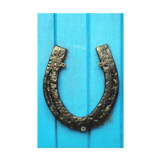 black horseshoe nailed to blue door canvas print