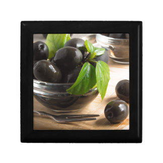 Black olives in a glass bowl on the old vintage jewelry box