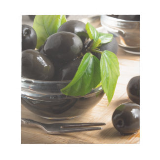 Black olives in a glass bowl on the old vintage notepad