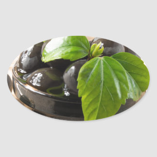 Black olives on a table and glass cups with oil oval sticker