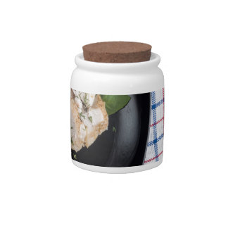 Black plate and baked slices of chicken meat candy jar