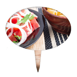 Black plate with fresh salad of tomatoes, onions cake topper