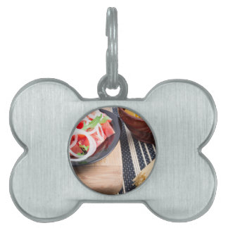Black plate with fresh salad of tomatoes, onions pet tag