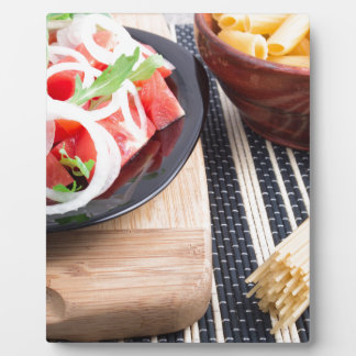 Black plate with fresh salad of tomatoes, onions plaque