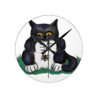 Black Tuxedo Kitten Finds a Garden Spider Round Clocks