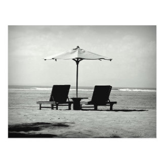 Black & white photo of two deck chairs on a beach postcard
