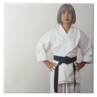 Blackbelt femenino maduro del karate, retrato azulejo cuadrado grande