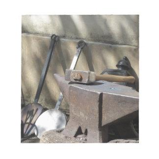 Blacksmith hammer resting on the anvil notepad