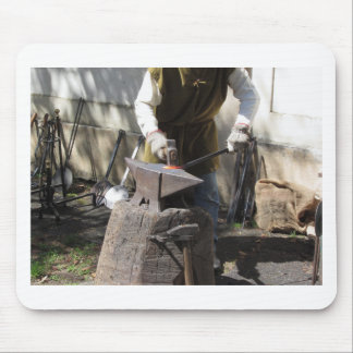 Blacksmith manually forging the molten metal mouse pad