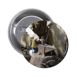 Blacksmith manually forging the molten metal pinback button