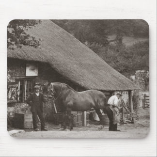 Blacksmith shoeing a horse mousepad