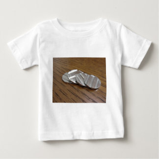 Blank metallic coins on wooden table baby T-Shirt