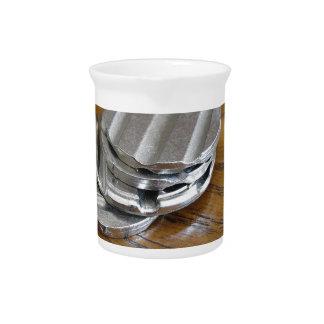 Blank metallic coins on wooden table beverage pitcher