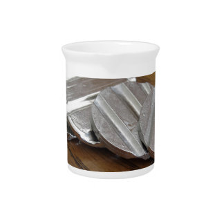 Blank metallic coins on wooden table drink pitcher