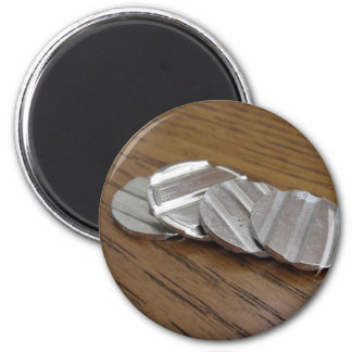 Blank metallic coins on wooden table magnet