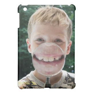 blond boy behind magnifying glass smiling iPad mini case