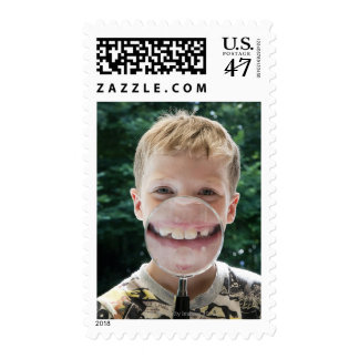 blond boy behind magnifying glass smiling postage