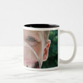 blond boy behind magnifying glass smiling Two-Tone coffee mug