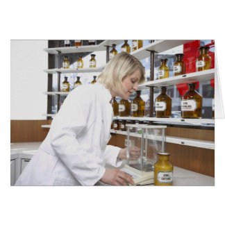 Blond pharmacist working in lab and smiling into card