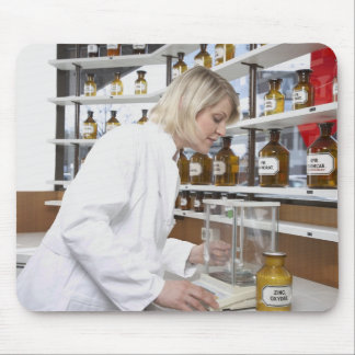 Blond pharmacist working in lab and smiling into mouse pads
