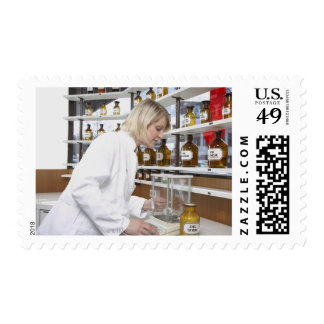 Blond pharmacist working in lab and smiling into postage stamp