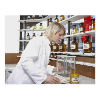 Blond pharmacist working in lab and smiling into postcard