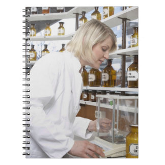 Blond pharmacist working in lab and smiling into spiral notebook