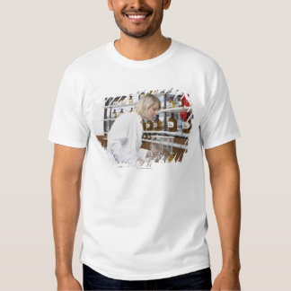 Blond pharmacist working in lab and smiling into t shirt
