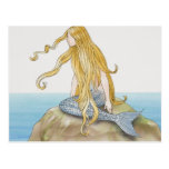 Blonde mermaid sitting on sea rock, side view. post card
