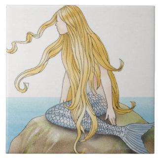 Blonde mermaid sitting on sea rock, side view. large square tile