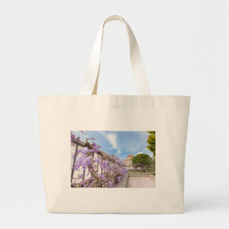 Blooming blue Wisteria sinensis on fence in Greece Large Tote Bag