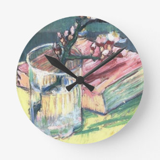 Blossoming Almond Branch in a glass and a book Round Clock