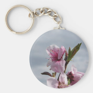Blossoming peach tree against the cloudy sky keychain