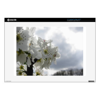 Blossoming pear tree against the cloudy sky skins for laptops