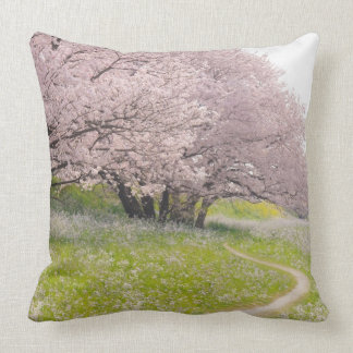 Blossoming Yoshino cherry trees in a field of Throw Pillow
